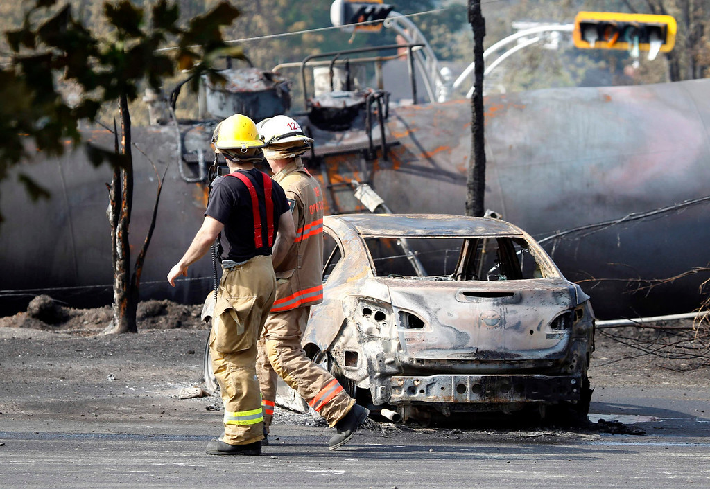 Description of . Firefighters walk past a burnt out vehicle near the train derailment in Lac Megantic, Quebec, July 7, 2013.  A driverless freight train carrying tankers of petroleum products derailed at high speed and exploded into a giant fireball in the middle of the small Canadian town of Lac-Megantic early on Saturday, destroying dozens of buildings and leaving an unknown number of people feared missing.  REUTERS/Christinne Muschi