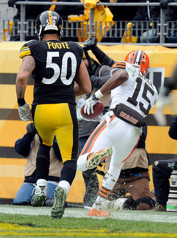 Description of . Cleveland Browns wide receiver Greg Little (15) makes a catch for a touchdown past Pittsburgh Steelers inside linebacker Larry Foote (50) in the third quarter of an NFL football game on Sunday, Dec. 30, 2012, in Pittsburgh. (AP Photo/Don Wright)