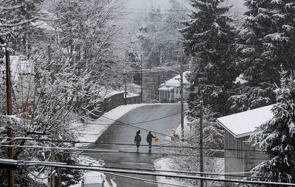Description of . Two men walk with snow shovels down Richwood Avenue in Morgantown, W.Va., on Wednesday, March 6, 2013.   (AP Photo/David Smith)