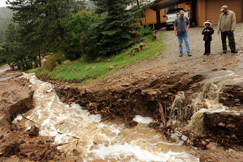 Description of . RAYMOND , CO - SEPTEMBER 12: Homeowner Brad DeHaan, right, with his daughter, Elise, 8, and neighbor Kevin Duffy, check out the flooding damage to the road that leads to their houses on Conifer Hill Road in the roadside community of Riverside, about 12 miles west of Lyons, Colo. along Highway 7 on September 12, 2013.  Heavy and continuous rains have created devastating and major flooding in many mountain communities. Some areas have had over 10 inches of rain in the last 24-48 hours.  (Photo By Helen H. Richardson/ The Denver Post)