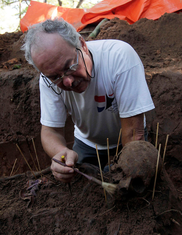 Description of . Argentine forensic expert Rogelio Agustin Goiburu excavates human remains discovered in the grounds of a police barracks in Asuncion on March 21, 2013. According to the researchers, 15 more skeleton remains, likely to be victims of the 1954 to 1989 dictatorship under Alfredo Stroessner, were found in the last two days. Goiburu\'s father, Augustin Goiburu, was arrested in Argentina during the Dirty War and brought to Paraguay where he disappeared and was presumed killed. REUTERS/Jorge Adorno