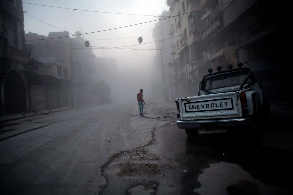 Description of . A Syrian man walks amid a street covered with dust following a reported air strike by government forces in the old city of Aleppo on July 21, 2014. Aleppo was Syria's most populous city before the conflict, but it is now a major battle zone split into areas controlled by the rebels concentrated in the east and those held by the government mainly in the west. AHMED DEEB/AFP/Getty Images