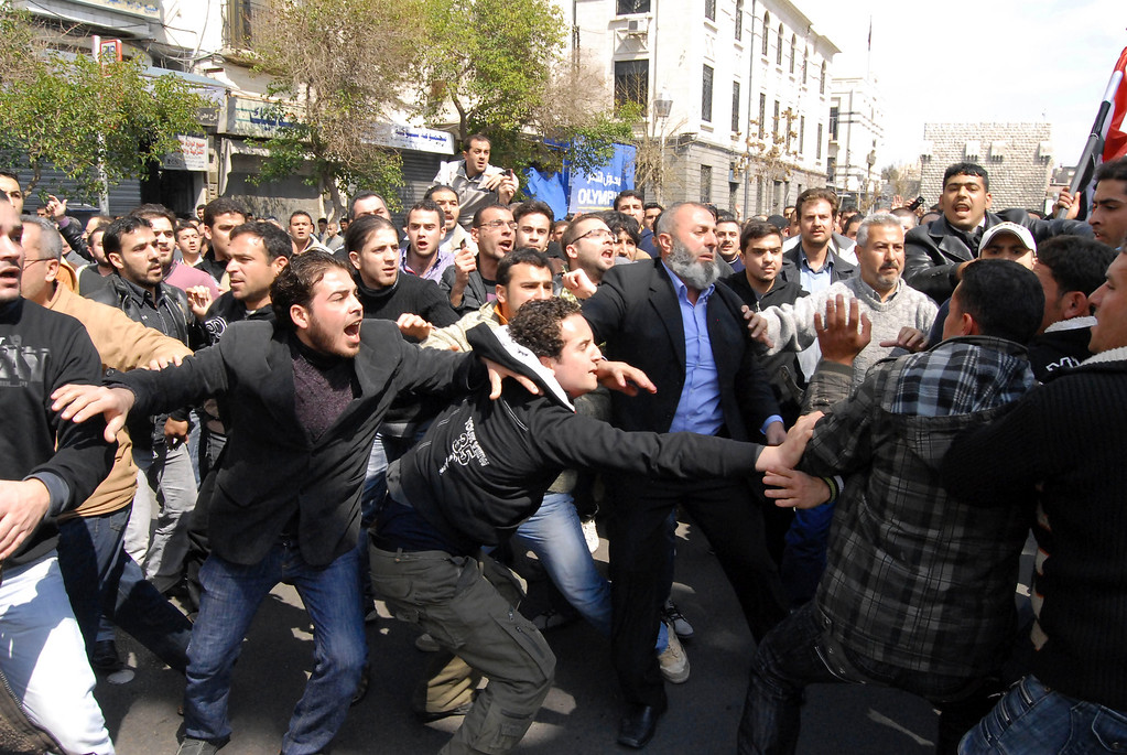 Description of . Syrians anti and pro-Assad protesters clash after Friday prayers in Damascus, Syria, Friday, March 25, 2011. Thousands of Syrians took to the streets Friday demanding reforms and mourning dozens of protesters who were killed during a violent, week long crackdown that has brought extraordinary pressure on the country's autocratic regime, activists and witnesses said. (AP Photo/Muzaffar Salman)