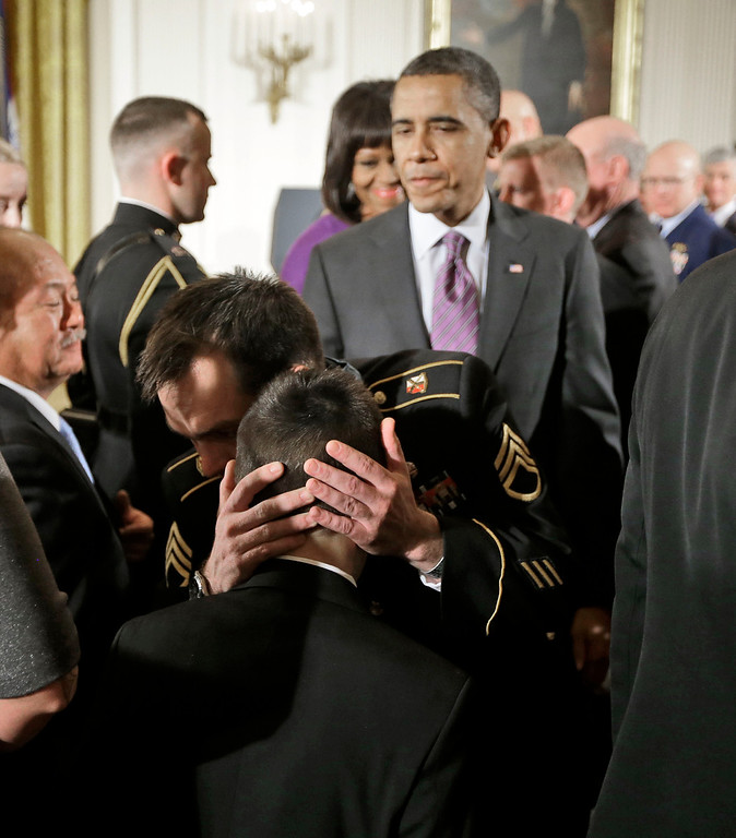 Description of . President Barack Obama watches as Medal of Honor recipient retired Staff Sgt. Clinton Romesha, facing camera, hugs MacAidan Gallegos, son of the late Sgt. Justin Gallegos, following Romesha's medal of honor ceremony in the East Room of the White House in Washington, Monday, Feb. 11, 2013. Sgt. Gallegos was one of eight who died as Romeshan fought back an intense daylong barrage by enemy fighters as the Taliban descended on Combat Outpost Keating in the mountains near the Pakistan border on Oct. 3, 2009.(AP Photo/Pablo Martinez Monsivais)