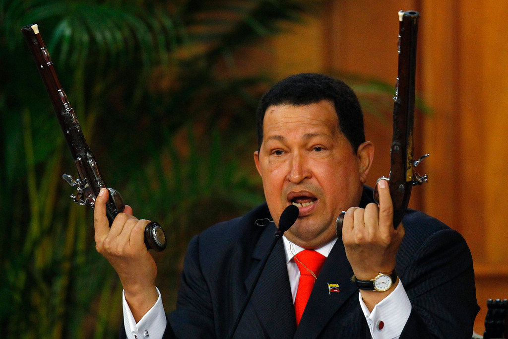 Description of . Venezuelan President Hugo Chavez shows the pistols of independence hero Simon Bolivar during a ceremony to mark the his birthday in Caracas July 24, 2012. Chavez unveiled a 3D image of South America's 19th century independence hero Bolivar on Tuesday, based on bones he had exhumed two years ago to test a theory that Bolivar was murdered. REUTERS/Carlos Garcia Rawlins