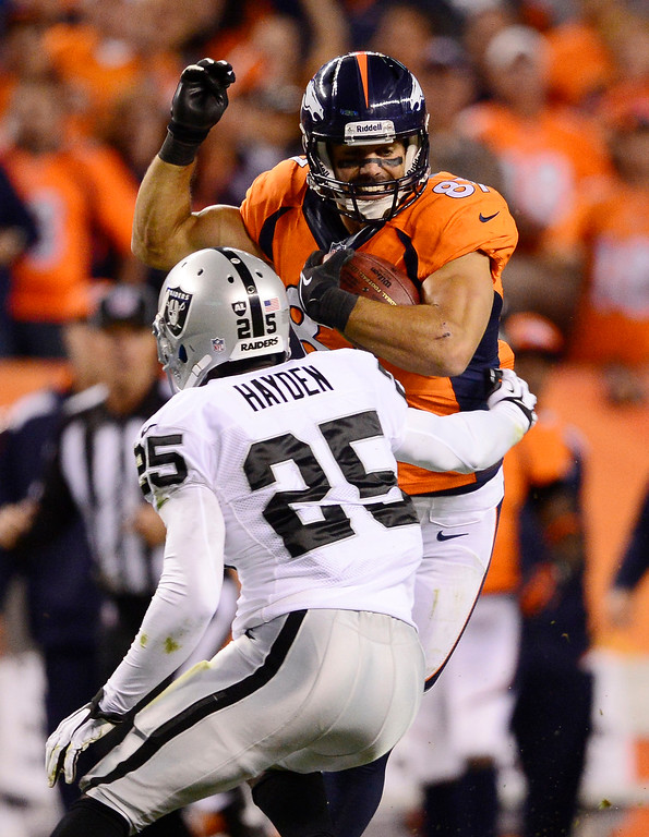 . Denver Broncos wide receiver Eric Decker (87) breaks a tackle by Oakland Raiders cornerback DJ Hayden (25) in the second quarter for a 61-yard play. The Denver Broncos took on the Oakland Raiders at Sports Authority Field at Mile High in Denver on September 23, 2013. (Photo by AAron Ontiveroz/The Denver Post)