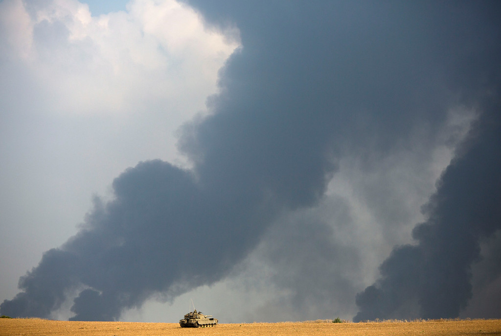 Description of . An Israeli tank sits in a field as heavy smoke rises from the Gaza Strip Tuesday, July 22, 2014. Israeli airstrikes pummeled a wide range of targets in the Gaza Strip on Tuesday as the U.N. chief and the U.S. secretary of state began an intensive effort to end more than two weeks of fighting that has killed hundreds of Palestinians and tens of Israelis. (AP Photo/Dusan Vranic)