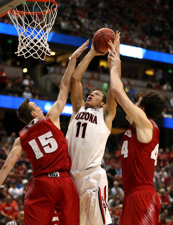 Description of . Aaron Gordon #11 of the Arizona Wildcats goes up for a shot against Sam Dekker #15 and Frank Kaminsky #44 of the Wisconsin Badgers in the second half during the West Regional Final of the 2014 NCAA Men's Basketball Tournament at the Honda Center on March 29, 2014 in Anaheim, California.  (Photo by Jeff Gross/Getty Images)