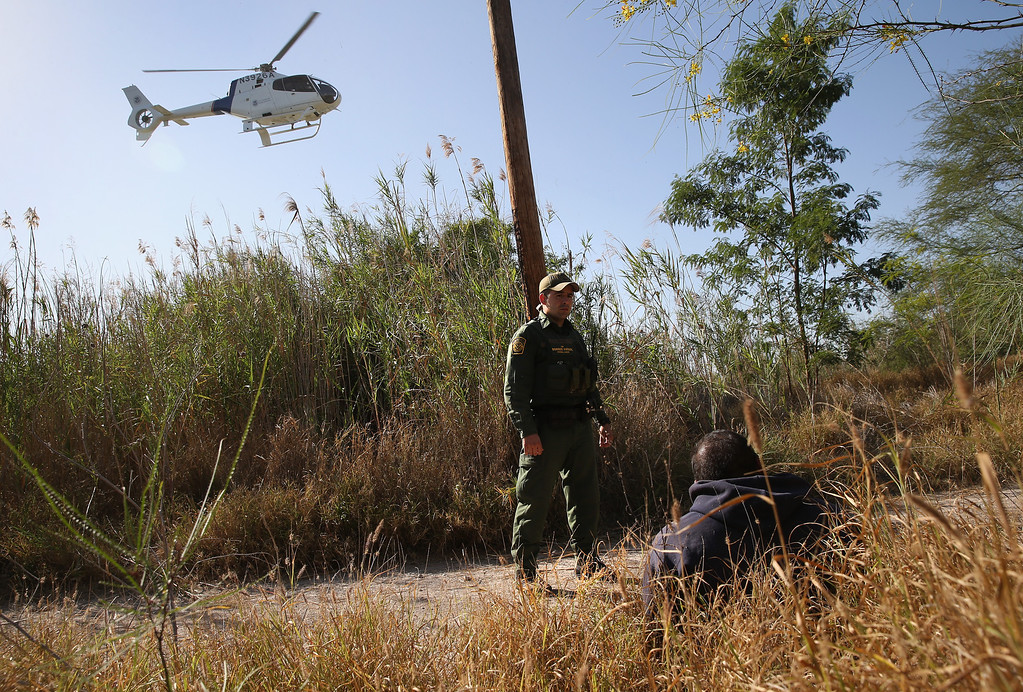 Description of . MISSION, TX - APRIL 11:  A U.S. Border Patrol agent guards a suspected drug smuggler on April 11, 2013 in Mission, Texas. Border Patrol agents with helicopter support from the Office of Air and Marine broke up a smuggling shipment of marijuana being transported across the border from Mexico into Texas. In addition to heavy drug smuggling in the area, Border Patrol agents say they have also seen an additional surge in immigrant traffic in Texas\' Rio Grande Valley sector since immigration reform negotiations began this year in Washington D.C.  (Photo by John Moore/Getty Images)