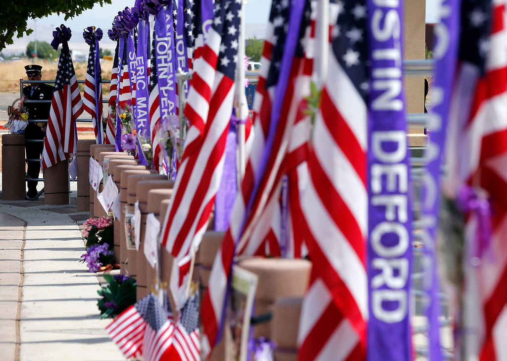 Description of . A firefighter waits at the entrance of a memorial for the fallen members of Prescott Fire Department's Granite Mountain Hotshots team in Prescott Valley, Arizona July 9, 2013. 30. REUTERS/Mike Blake