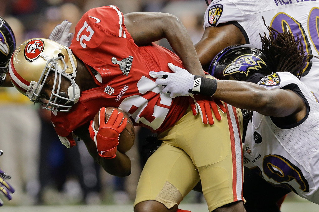 Description of . San Francisco 49ers running back Frank Gore (21) is tackled by Baltimore Ravens linebacker Dannell Ellerbe (59) in the first quarter of the NFL Super Bowl XLVII football game, Sunday, Feb. 3, 2013, in New Orleans. (AP Photo/Patrick Semansky)