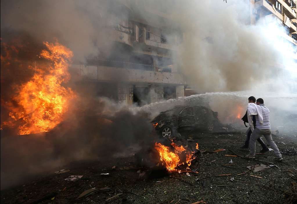 Description of . Two Lebanese men react in front of burned cars, at the scene where two explosions have struck near the Iranian Embassy killing many, in Beirut, Lebanon, Tuesday Nov. 19, 2013.  (AP Photo/Hussein Malla)