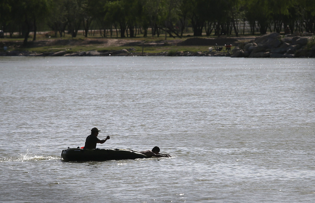 Description of . MISSION, TX - APRIL 11:  Suspected drug smugglers flee across the Rio Grande River into Mexico on April 11, 2013 in Mission, Texas. Their marijuana smuggling mission was broken up by U.S. Border Patrol agents with helicopter support from the Office of Air and Marine. In addition to the drug smuggling, Border Patrol agents say they have also seen an additional surge in immigrant traffic in Texas\' Rio Grande Valley sector since immigration reform negotiations began this year in Washington D.C.  (Photo by John Moore/Getty Images)