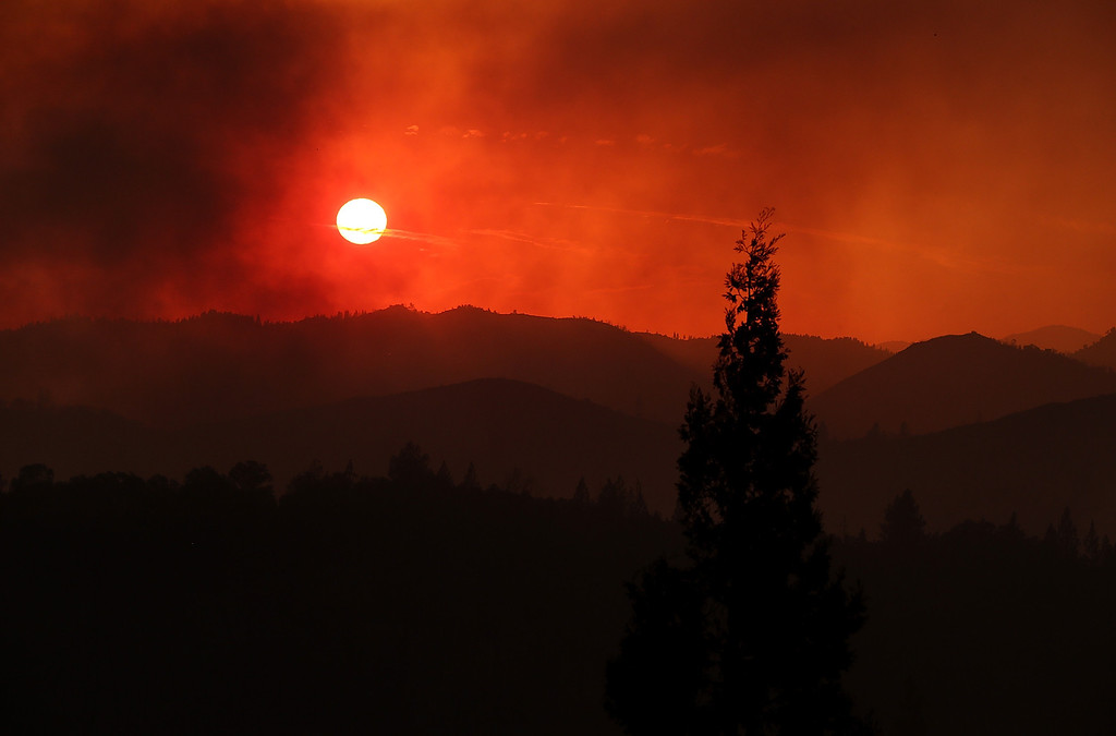 Description of . GROVELAND, CA - AUGUST 21:  The sun sets through heavy smoke from the Rim Fire on August 21, 2013 in Groveland, California. The Rim Fire continues to burn out of control and threatens 2,500 homes outside of Yosemite National Park. Over 400 firefighters are battling the blaze that is only 5 percent contained.  (Photo by Justin Sullivan/Getty Images)