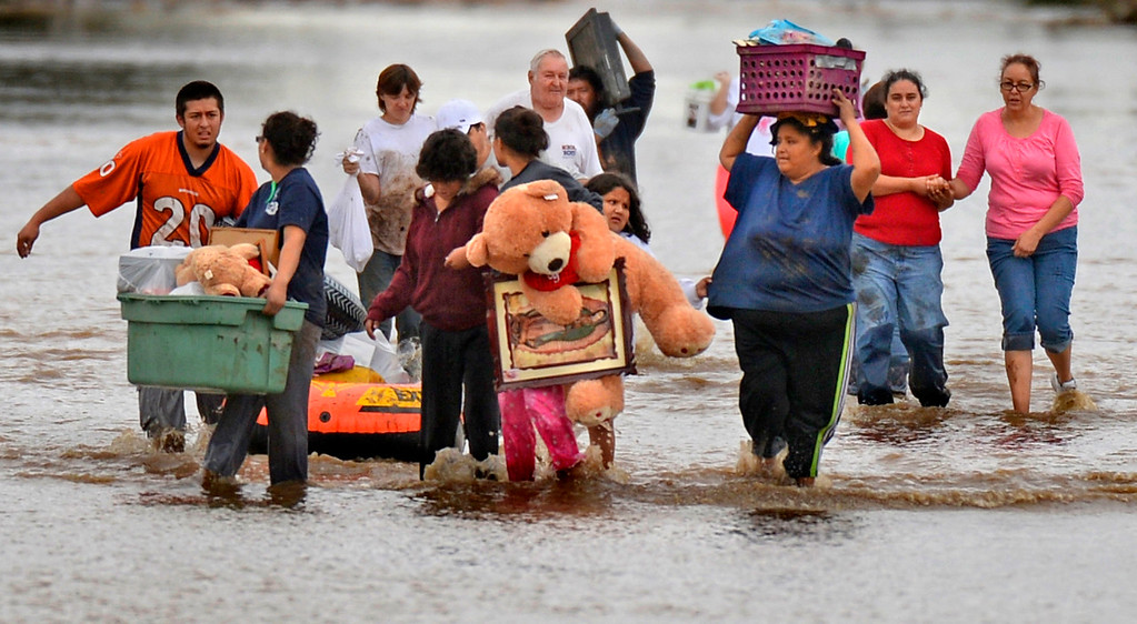 Description of . Residents of homes along 37th Street in Evans carry belongings from their flooded homes on Sept. 16, 2013. Evans remained under a no-flush order as 260 homes were totaled or damaged by the Colorado floods.