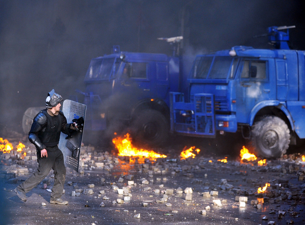 Description of . A anti-government protester clashes with riot police in central Kiev on February 18, 2014.  AFP PHOTO/GENYA SAVILOV/AFP/Getty Images