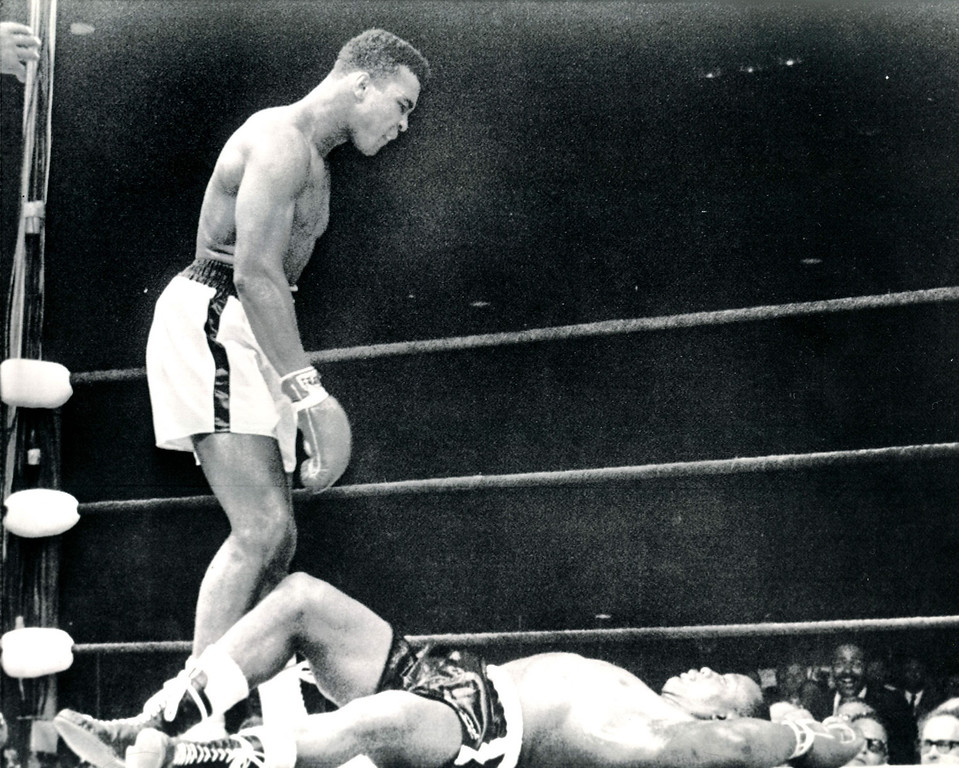 Description of . JUST ABOUT OVER-The heavyweight champion, one Cassius Clay, glowers at challenger Sonny Liston who lies stretched out on canvas in first and only round of a title bout.  Clay won on a KO.   Liston is stretched out on the deck after taking a right-hand punch from Clay.  The knockout at one minute of the first round was the shortest ever recorded in a heavy-weight championship fight.  The crowd in the Lewiston, Maine arena screamed