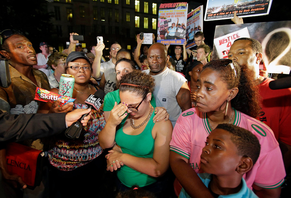 Description of . Demonstrators outside the Seminole County Courthouse react after hearing the verdict of not guilty in the trial of George Zimmerman, Saturday, July 13, 2013, in Sanford, Fla. Zimmerman had been charged with the 2012 shooting death of Trayvon Martin. (AP Photo/John Raoux)