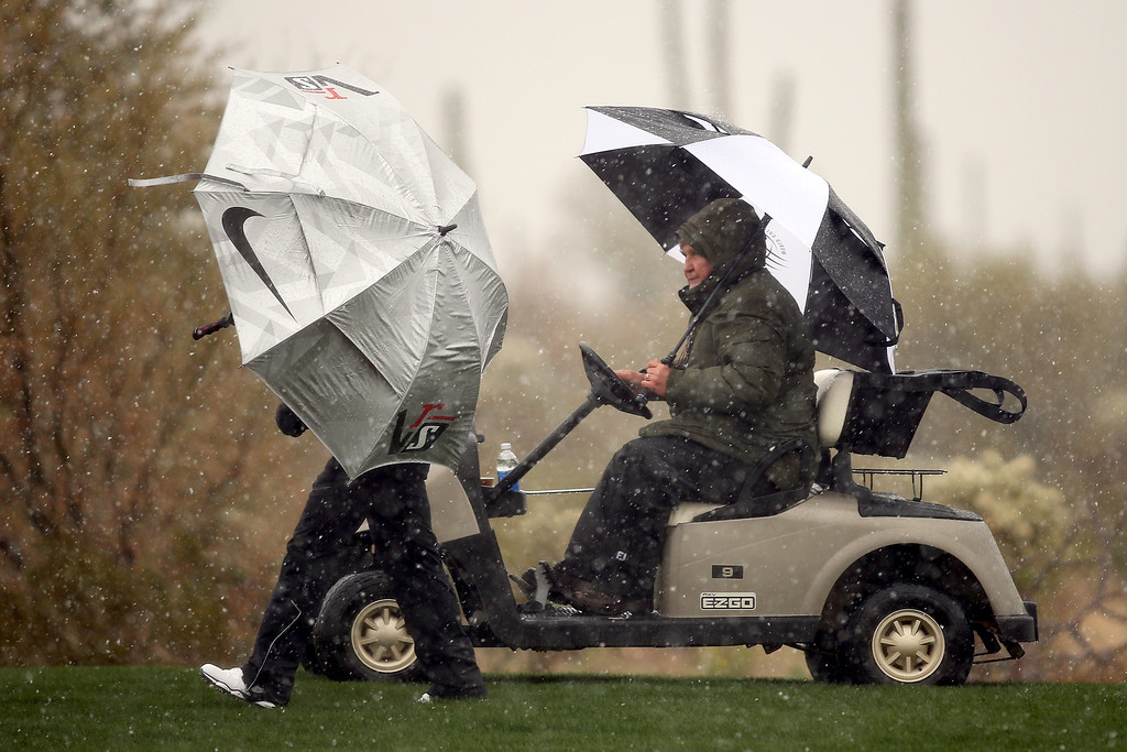 Description of . MARANA, AZ - FEBRUARY 20:  Mark Russell (R), the PGA TOUR's Vice President of Rules and Competition talks with Thorbjorn Olesen of Denmark as Olesen stands under an umbrella to avoid the snow and rain, play was suspended due to weather, during the first round of the World Golf Championships - Accenture Match Play at the Golf Club at Dove Mountain on February 20, 2013 in Marana, Arizona.  (Photo by Darren Carroll/Getty Images)