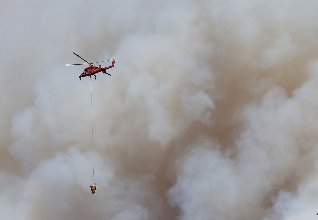 Description of . GROVELAND, CA - AUGUST 22:  A firefighting helicopter flies in front of a plume of smoke from the Rim Fire on August 22, 2013 in Groveland, California. The Rim Fire continues to burn out of control and threatens 2,500 homes outside of Yosemite National Park. Over 1,000 firefighters are battling the blaze that was reduced to only 2 percent containment after it nearly tripled in size overnight.  (Photo by Justin Sullivan/Getty Images)
