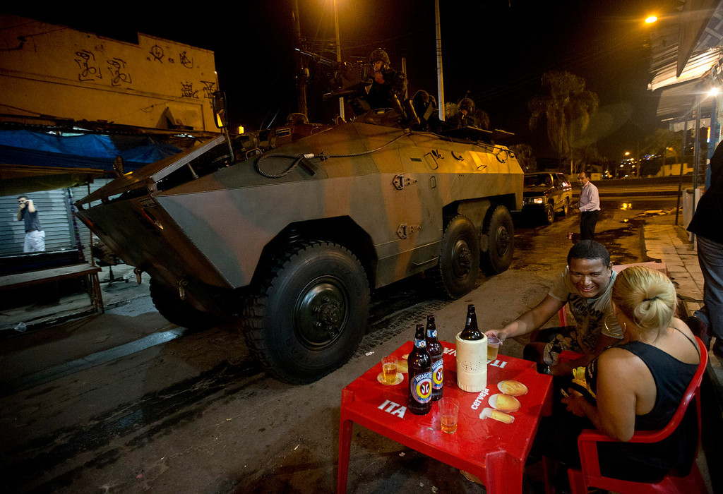 Description of . A couple drink beer while Army soldiers enter  to occupy the Mare slum complex in Rio de Janeiro, Brazil, Saturday, April 5, 2014. More than 2,000 Brazilian Army soldiers moved into the Mare slum complex early Saturday in a bid to improve security and drive out the heavily armed drug gangs that have ruled the sprawling slum for decades. (AP Photo/Silvia Izquierdo)