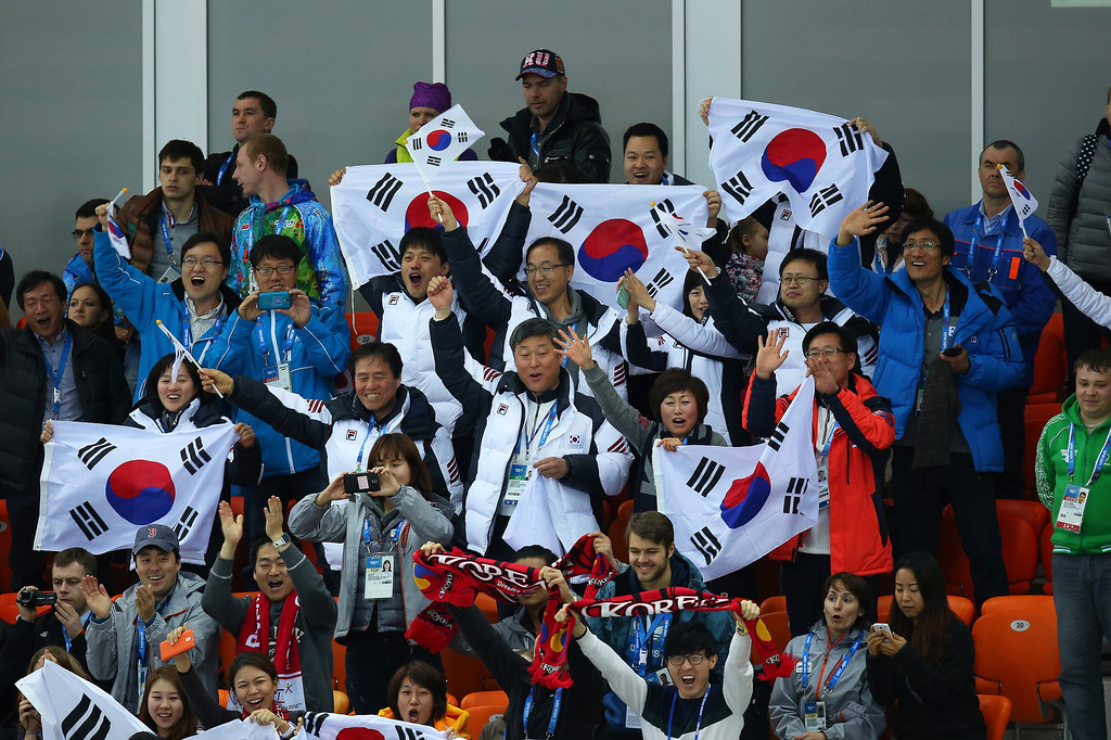 Description of . South Korean fans celebrate the gold medal of Sang Hwa Lee of South Korea during the Women\'s 500m Race 2 of 2 Speed Skating event during day 4 of the Sochi 2014 Winter Olympics at at Adler Arena Skating Center on February 11, 2014 in Sochi, Russia.  (Photo by Quinn Rooney/Getty Images)