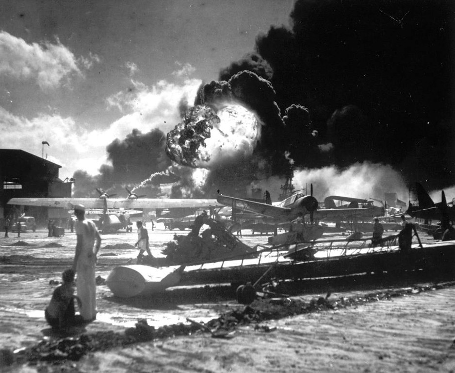 Description of . In this Dec. 7, 1941 file photo, sailors stand among wrecked airplanes at Ford Island Naval Air Station as they watch the explosion of the USS Shaw in the background, during the Japanese surprise attack on Pearl Harbor, Hawaii. Wednesday marks the 70th anniversary of the attack that brought the United States into World War II. (AP File Photo)