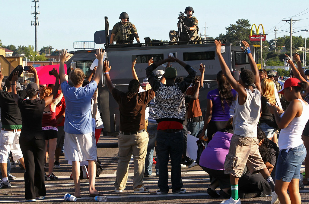 Description of . Protesters raise their hands in front of police atop an armored vehicle in Ferguson, Mo. on Wednesday, Aug. 13, 2014. On Saturday, Aug. 9, 2014, a police officer fatally shot Michael Brown, an unarmed black teenager, in the St. Louis suburb. (AP Photo/St. Louis Post-Dispatch, J.B. Forbes)