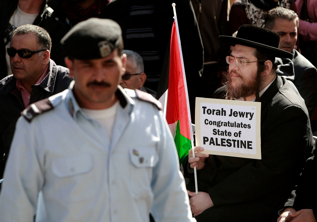 Description of . A Hassidic Jew holds a Palestinian flag and a sign during a rally supporting the Palestinian UN bid for observer state status, in the West bank city of Ramallah, Thursday, Nov. 29, 2012. The Palestinians are certain to win U.N. recognition as a state on Thursday but success could exact a high price: delaying an independent state of Palestine because of Israel's vehement opposition. (AP Photo/Majdi Mohammed)