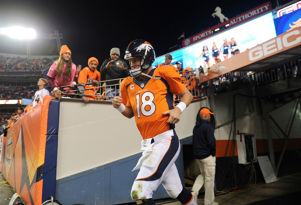 Description of . Denver Broncos quarterback Peyton Manning (18) runs out onto the filed after halftime. The Denver Broncos took on the Oakland Raiders at Sports Authority Field at Mile High in Denver on September 23, 2013. (Photo by Joe Amon/The Denver Post)