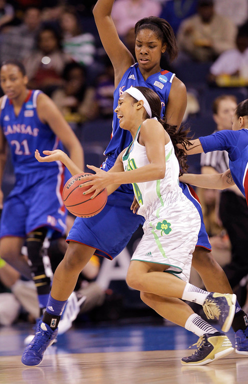 Description of . Notre Dame guard Skylar Diggins (4) slams into Kansas forward Chelsea Gardner (15) during the first half of a regional semi-final of the NCAA college basketball tournament Sunday  March 31, 2013 in Norfolk, Va.  (AP Photo/Steve Helber)