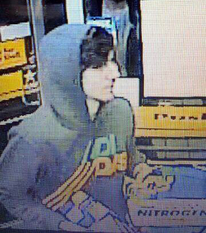 Description of . This surveillance photo released via Twitter Friday, April 19, 2013 by the Boston Police Department shows a suspect entering a convenience store that police are pursuing in Watertown, Mass.  Police say he is one of two suspects in the fatal shooting of an MIT police officer and tied to the Boston Marathon bombing. (AP Photo/Boston Police Department)