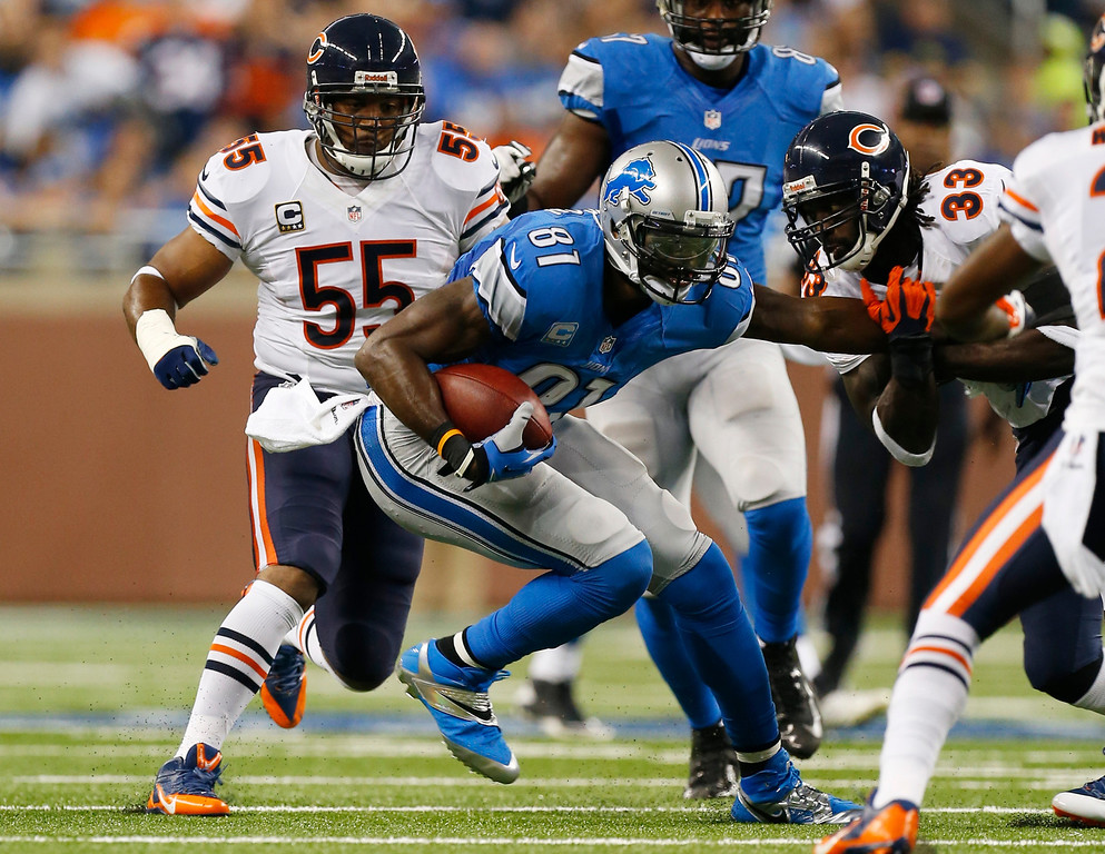 Description of . Chicago Bears cornerback Charles Tillman (33) and outside linebacker Lance Briggs (55) close in on Detroit Lions wide receiver Calvin Johnson (81) during the first quarter of an NFL football game at Ford Field in Detroit, Sunday, Sept. 29, 2013. (AP Photo/Paul Sancya)