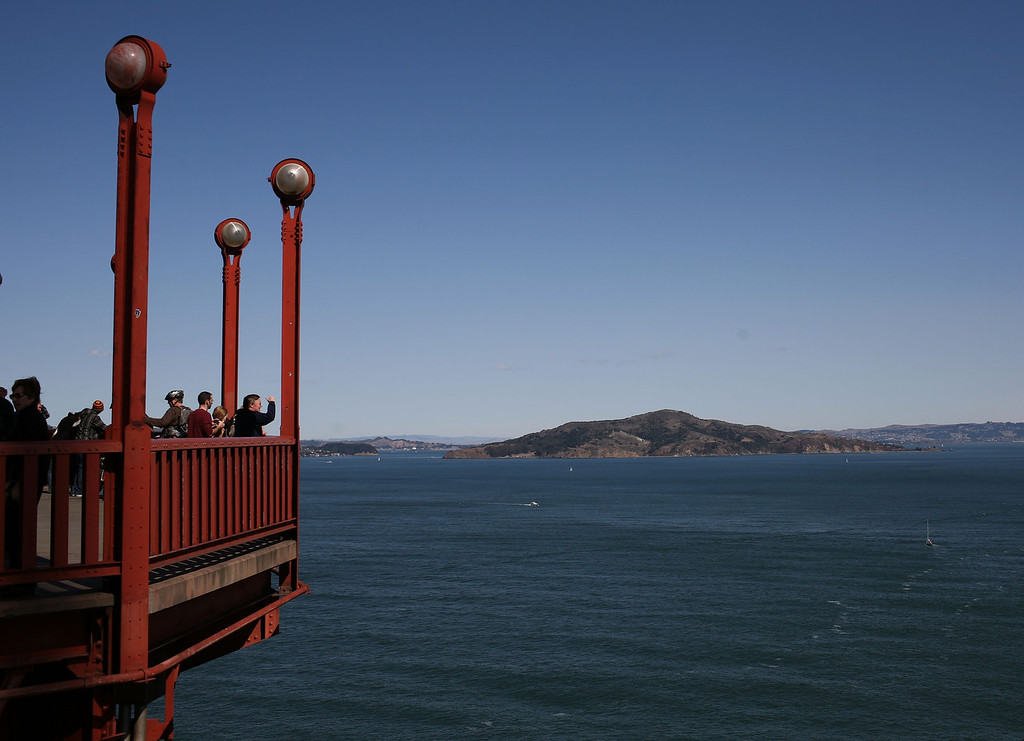 Description of . Tourists take photos from a vantage point on the span of the Golden Gate Bridge October 10, 2008 in San Francisco, California. (Photo by Justin Sullivan/Getty Images)