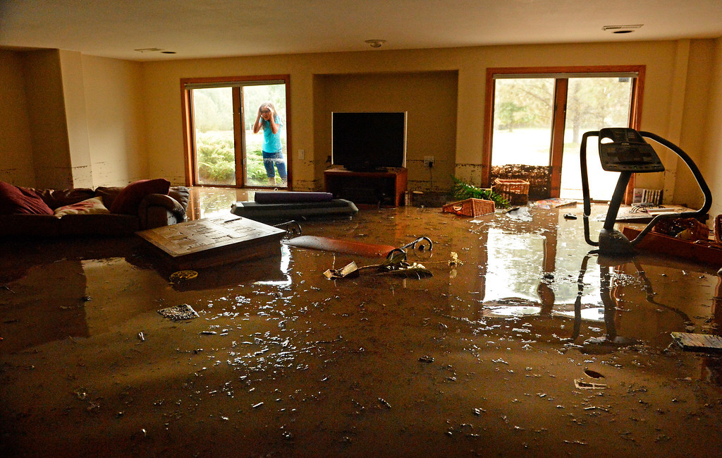 Description of . Casey Roy, 9, looks through an outside window at the damage in her families basement, at Premier Place in north Boulder, flood water was about three-feet in the basement, September 12, 2013. (Photo By RJ Sangosti/The Denver Post)