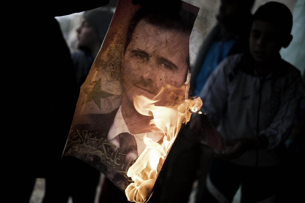 Description of . A member of the Free Syrian Army holds a burning portrait of embattled President Bashar al-Assad in Al-Qsair, 25kms southwest of the flashpoint city Homs, on January 25, 2012. Although heavily outnumbered and outgunned, the Free Syrian Army has increasingly launched bold attacks against regime forces and managed to seize control of some neighbourhoods of Homs. Alessio Romenzi/AFP/Getty Images