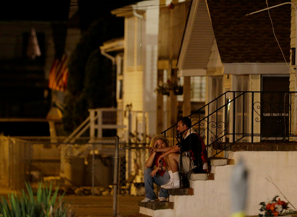 Description of . People sit on the steps of a home near the Seaside Park boardwalk, where earlier in the day a massive fire engulfed businesses on the boardwalk, Thursday, Sept. 12, 2013, in Seaside Park, N.J. The fire, which apparently started near an ice cream shop and spread several blocks, hit the recently repaired boardwalk, which was damaged last year by Superstorm Sandy. There were no other early reports of any injuries. (AP Photo/Julio Cortez)