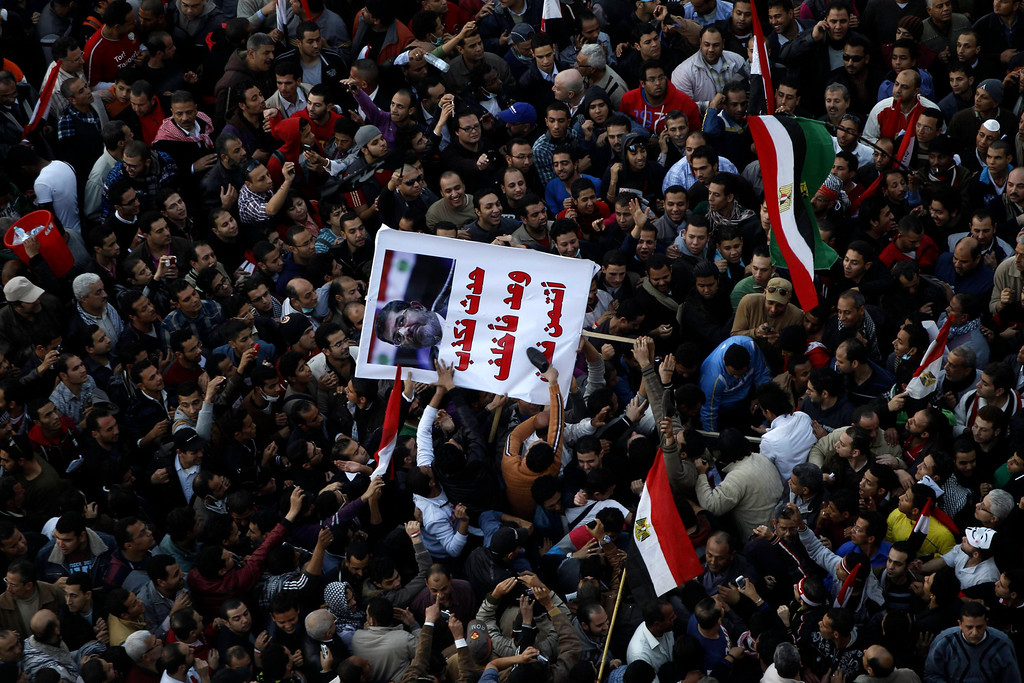 ". Protesters opposing Egyptian President Mohamed Mursi shout slogans and hit a poster of Mursi that reads ""If he speaks, he always lies\"" with shoes at Tahrir Square in Cairo January 25, 2013. Hundreds of youths fought Egyptian police in Cairo on Friday on the second anniversary of the revolt that toppled Hosni Mubarak and brought the election of an Islamist president who protesters accuse of riding roughshod over the new democracy. Opponents of Mursi and his Muslim Brotherhood allies began massing in Cairo\'s Tahrir Square to revive the demands of a revolution they say has been betrayed by Islamists. REUTERS/Amr Abdallah Dalsh"