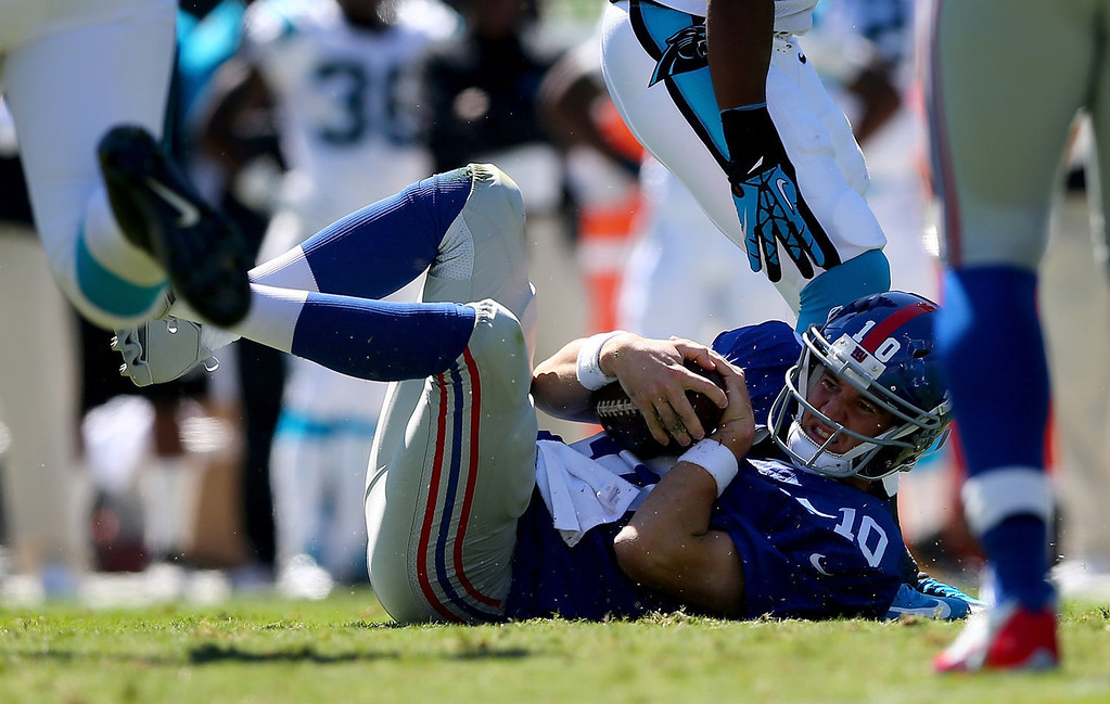 Description of . Eli Manning #10 of the New York Giants is knocked to the ground during their game against the Carolina Panthers at Bank of America Stadium on September 22, 2013 in Charlotte, North Carolina.  (Photo by Streeter Lecka/Getty Images)