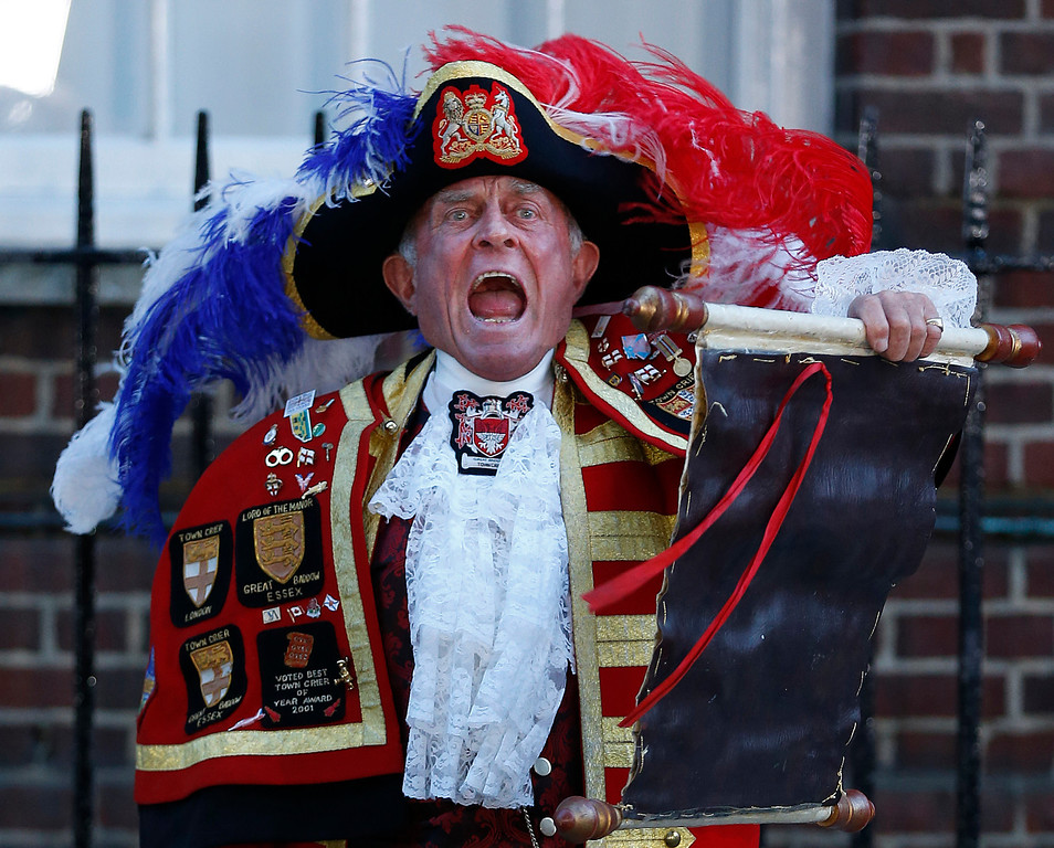 Description of . Tony Appleton, a town crier,  announces the birth of the royal baby, outside St. Mary's Hospital exclusive Lindo Wing in London, Monday, July 22, 2013.  (AP Photo/Lefteris Pitarakis)