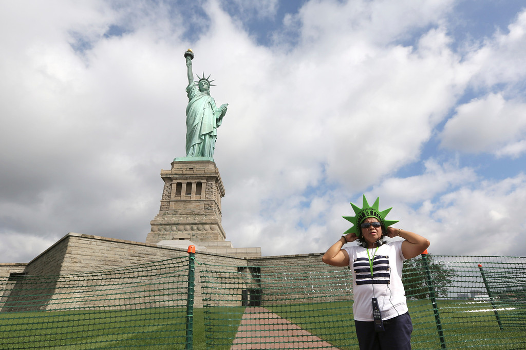 Description of . Leticia Baes, of the Phillipines, poses for a photo at the bases of the Statue of Liberty, Thursday, July 4, 2013 at  in New York. The Statue of Liberty finally reopened on the Fourth of July months after Superstorm Sandy swamped its little island in New York Harbor as Americans across the country marked the holiday with fireworks and barbecues. (AP Photo/Mary Altaffer)
