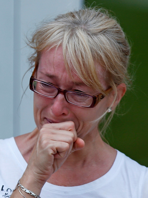Description of . A woman cries as she leaves the Polyvalente Montignac, the school sheltering the people who were forced to leave their houses after the explosion, in Lac Megantic, July 7, 2013. Several people were missing after four tank cars of petroleum products exploded in the middle of a small town in the Canadian province of Quebec early on Saturday in a fiery blast that destroyed dozens of buildings.  REUTERS/Mathieu Belanger