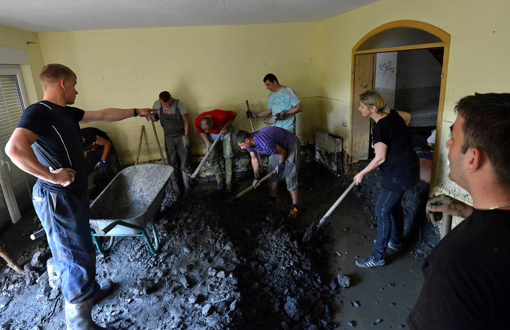 Description of . Residents clean a house of mud and rubble after a landslide at the village of Topcic Polje, near the Bosnian town of Zenica, 90 kilometers north of Sarajevo, Bosnia-Herzegovina, Tuesday May 20, 2014. Bosnia, Serbia and Croatia have been hit by the worst flooding in more than 100 years, forcing half a million people out of their homes and leading to more than three dozen deaths. (AP Photo/Sulejman Omerbasic)