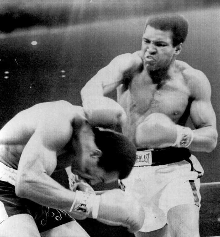 "Description of . A mean looking Muhammad Ali throws a left to the head of a ducking Ken Norton during the first round of a return match between Norton and Ali in what is being billed as the ""Battle of the Broken Jaw.""	1973. Denver Post Library photo archive"
