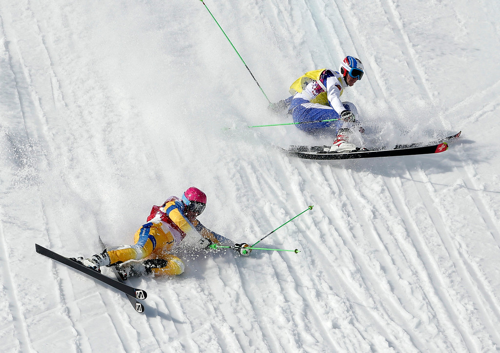 Description of . Sweden's Victor Oehling Norberg, left, and Russia's Igor Korotkov crash during a men's ski cross heat at the Rosa Khutor Extreme Park, at the 2014 Winter Olympics, Thursday, Feb. 20, 2014, in Krasnaya Polyana, Russia. (AP Photo/Andy Wong)