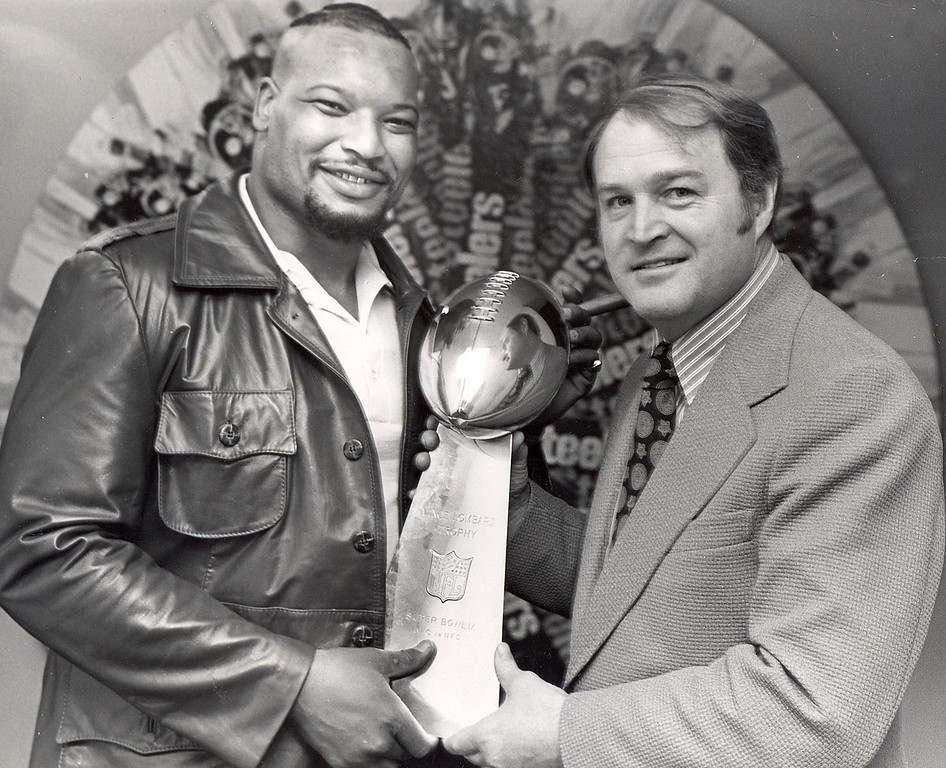 Description of . Pittsburgh Steelers' head coach Chuck Noll, right, and his defensive tackle Ernie Holmes, pose with the championship Super Bowl IX trophy in the Steelers' Pittsburgh dressing room following their victory over the Minnesota Vikings, Jan. 14, 1975.  (AP Photo)
