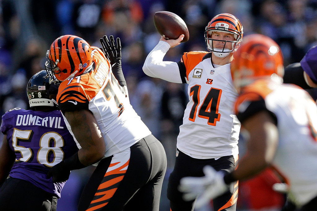 Description of . Cincinnati Bengals quarterback Andy Dalton passes the ball as Baltimore Ravens outside linebacker Elvis Dumervil (58) closes in during the first half of a NFL football game in Baltimore, Sunday, Nov. 10, 2013. (AP Photo/Patrick Semansky)
