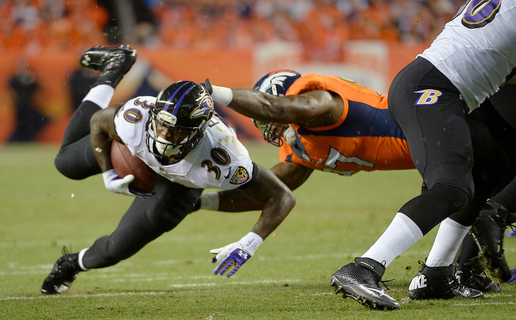 Description of . Baltimore Ravens running back Bernard Pierce (30) is taken down in the first quarter.  (Photo by Joe Amon/The Denver Post)
