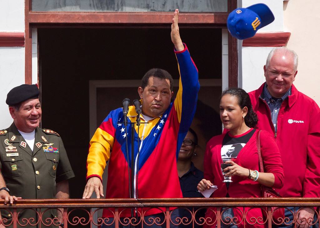 Description of . Venezuela's President Hugo Chavez throws a Magallanes baseball cap to supporters from a balcony at Miraflores presidential palace in Caracas, Venezuela, Saturday, March 17, 2012. Chavez returned to Venezuela Friday nearly three weeks after undergoing cancer surgery in Cuba.  At left is Defense Minister Henry Rangel Silva, and at right is Chavez's daughter Rosa Virginia and Oil Minister Rafael Ramirez. (AP Photo/Ariana Cubillos)