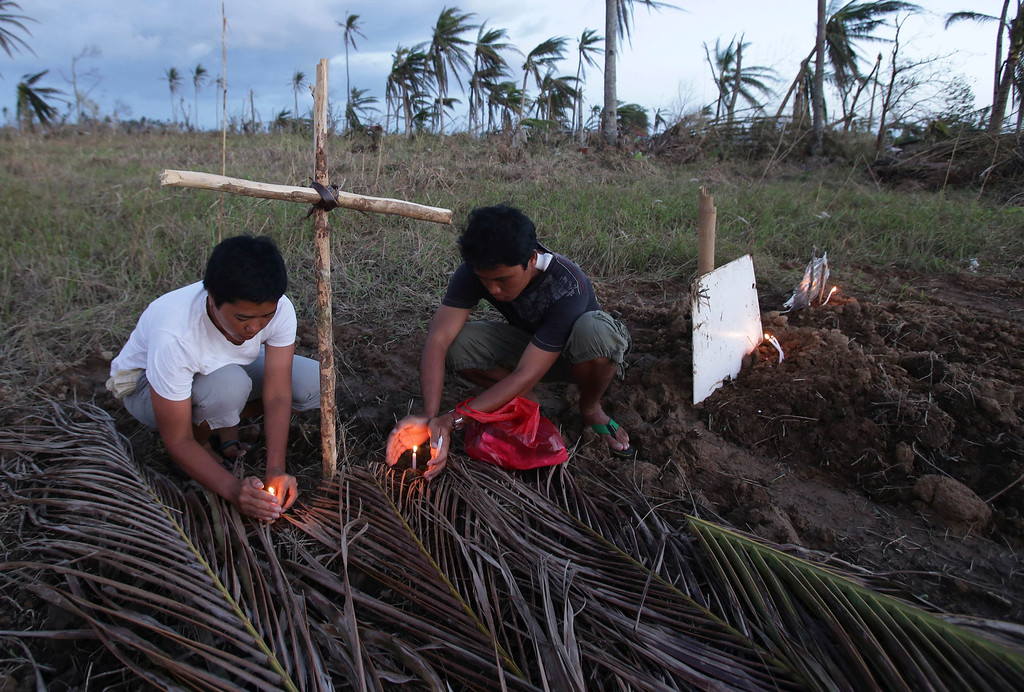 Description of . Relatives light candles for victims of Typhoon Haiyan at a makeshift grave site on a field in Palo town, Leyte province, central Philippines on Saturday, Nov. 16, 2013. (AP Photo/Aaron Favila)
